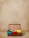 Retro tourist luggage with colorful clothes and copyspace Stock Images