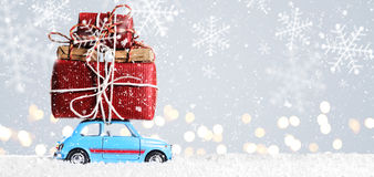 Retro toy car with christmas gifts. Blue retro toy car delivering Christmas or New Year gifts on festive gray background royalty free stock photo