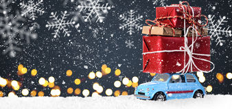 Retro toy car with christmas gifts. Blue retro toy car delivering Christmas or New Year gifts on festive gray background stock photography