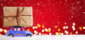 Retro toy car with christmas gifts. Blue retro toy car delivering Christmas or New Year gifts on festive red background stock images