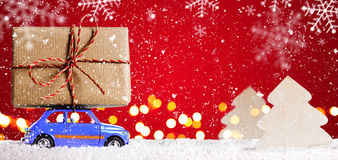 Retro toy car with christmas gifts. Blue retro toy car delivering Christmas or New Year gifts on festive red background stock photos