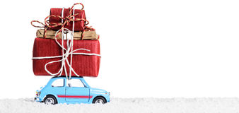 Retro toy car with christmas gifts. Blue retro toy car delivering Christmas or New Year gifts, isolated on white royalty free stock images