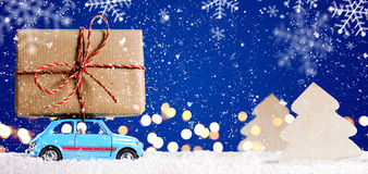 Retro toy car with christmas gifts. Retro toy car delivering Christmas or New Year gifts on festive blue background royalty free stock photos