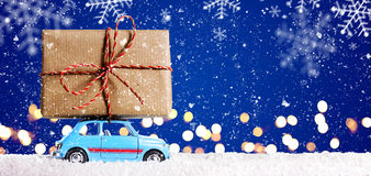 Retro toy car with christmas gifts. Retro toy car delivering Christmas or New Year gifts on festive blue background stock photo