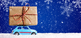 Retro toy car with christmas gifts. Retro toy car delivering Christmas or New Year gifts on festive blue background royalty free stock images