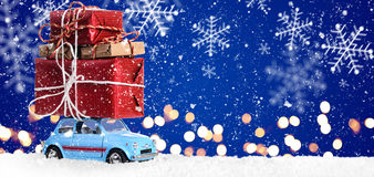 Retro toy car with christmas gifts. Retro toy car delivering Christmas or New Year gifts on festive blue background stock image