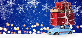 Retro toy car with christmas gifts. Retro toy car delivering Christmas or New Year gifts on festive blue background royalty free stock photography
