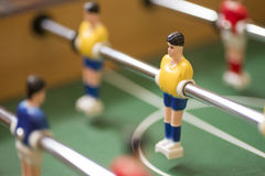 Retro toy football or soccer player. Suspended on a movable metal rod in a vintage board game, selective focus to one player Royalty Free Stock Photos