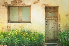 Retro träfönster och dörr för tappning på den gamla grungetegelstenväggen Royaltyfri Bild