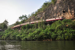 Retro train. Is slowly traveling on cliffs and trees on river Stock Photography