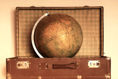 Retro Travel Concept With Globe. Travel concept with globe in the old dusty suitcase in retro style Royalty Free Stock Image