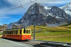 Retro treno turistico e fronte del nord di Eiger, Bernese Oberland, Svizzera Fotografia Stock