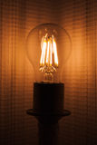 Retro tungsten lamp glowing in dark Stock Photo