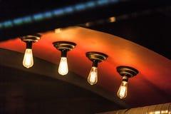 Retro tungsten lamps glowing in dark interior Stock Image