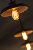 Retro tungsten lamps glowing over dark ceiling Royalty Free Stock Photos