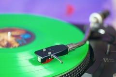 Retro turntable with green vinyl record Stock Photos