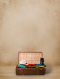 Retro turystyczny bagaż z kolorowymi ubraniami i copyspace ilustracji