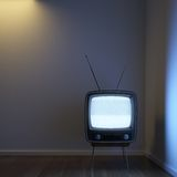 Retro TV alone in the corner. A single retro TV in a corner room showing signal noise with dramatic lighting setup to emphasize the concept of loneliness Stock Photos