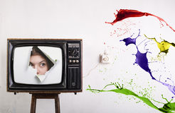 Retro TV and color. Retro TV face of a woman on the screen and bursts of color ink Stock Photography