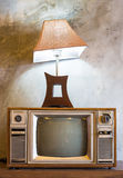 Retro TV con il caso e la lanterna di legno nella sala con la carta da parati d'annata Fotografia Stock