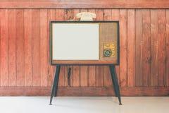 Retro TV con il fondo di legno della parete Immagine Stock