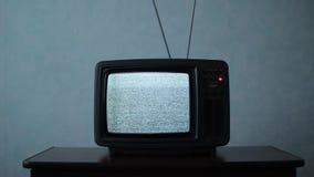 Retro TV con rumore bianco in una stanza scura stock footage
