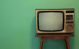 A retro TV. On old wooden table with green paint wall background Stock Photography