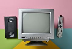 Retro tv, remote controller, vhs, on pastel background.  royalty free stock photos