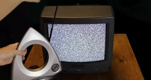 Hands adjusting rabbit ears for retro TV with snow and sound stock video footage