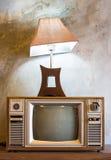 Retro tv z drewnianą skrzynką i lampionem w pokoju z rocznik tapetą Zdjęcie Stock