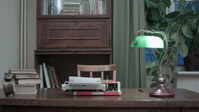 Retro typewriter with books and green lamp on the table stock video