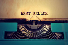 Retro typewritter and text best seller written with it. Closeup of a blue retro typewritter and the text best seller written with it in a yellowish foil stock images