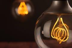 Retro uitstekende gloeilamp met geleide technologie bult-binnen op warme lichtgele tint en zwarte achtergrond, energie - besparin stock afbeeldingen