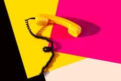 Retro uitstekende telefoonzaktelefoon gele rozerode purpere plastic oranje diskoachtergrond oude stijlschaduw 90 zwarte stock afbeeldingen
