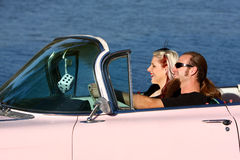 Retro unga par i rosa Cadillac Royaltyfri Foto