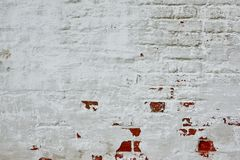 Retro- ungleiche Backsteinmauer mit Weiß gemaltem Gips-Hintergrund Stockbild