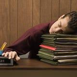 Retro uomo d'affari sovraccarico che dorme allo scrittorio. Fotografie Stock