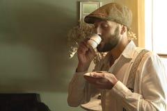 Retro uomo disegnato che assaggia un caffè in un ambiente d'annata fotografia stock libera da diritti