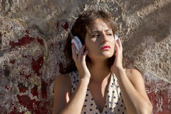 Retro urban music. A vintage dressed girl listing to music in a urban environment Stock Photography
