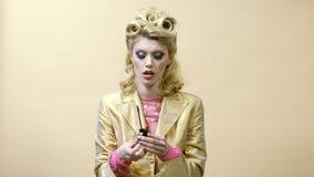 Retro utformad utvikningsbildkvinna på gul bakgrund Stiftet upp kvinna applicerar ?gonskugga, m?larf?rg?gonfrans Ögonskugga eller stock video