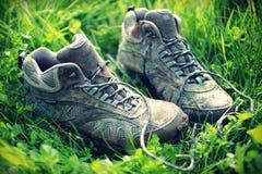 Retro- verblaßtes Foto von schmutzigen gehenden Stiefeln im grünen Gras Stockfoto