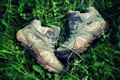 Retro- verblaßtes Foto von schmutzigen gehenden Stiefeln im grünen Gras Lizenzfreie Stockfotografie