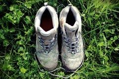 Retro- verblaßtes Foto von schmutzigen gehenden Stiefeln im grünen Gras Lizenzfreie Stockbilder