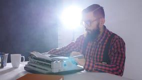 Retro- Verfasserkonzept Junger bärtiger stilvoller Mann, der auf alte Schreibmaschine schreibt stock footage