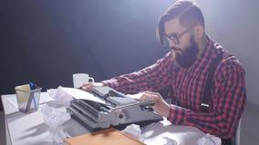 Retro- Verfasserkonzept Junger bärtiger stilvoller Mann, der auf alte Schreibmaschine schreibt stock video