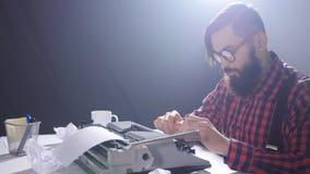 Retro- Verfasserkonzept Junger bärtiger stilvoller Mann, der auf alte Schreibmaschine schreibt stock video footage