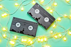 Retro vhs video tape. With bright glowing led garlands on blue background. Top view, minimalism royalty free stock photography