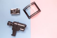 Flat lay of old fashioned camcorder, camera and photo frame against pastel background minimalistic concept. Retro vintage analog film camcorder, photo camera stock photo