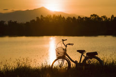 Retro vintage bicycle near the lake at sunset moment. silhouette bicycle at the sunset with grass field.big mountain and sunset. Background.journey concept stock photo