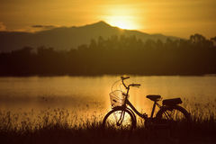 Retro vintage bicycle near the lake at sunset moment. silhouette bicycle at the sunset with grass field.big mountain and sunset. Background.journey concept royalty free stock images